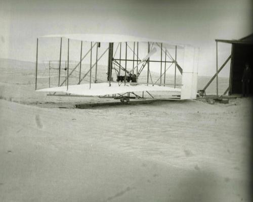 The 1903 powered aircraft outside its hangar in Kitty Hawk.  Wilbur stands at the right.  Photo courtesy of Smithsonian National Air and Space Museum.